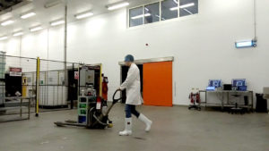 Operator walking the warehouse robot.